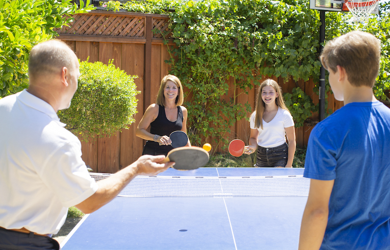 Family plays ping pong outdoors to have fun as a family